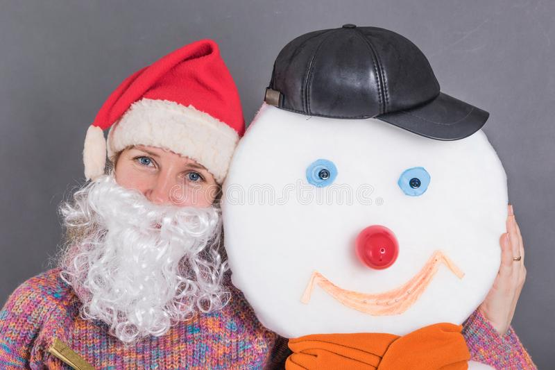 Cheerful adult woman with a Santa Claus beard embraces a snowman stock photography