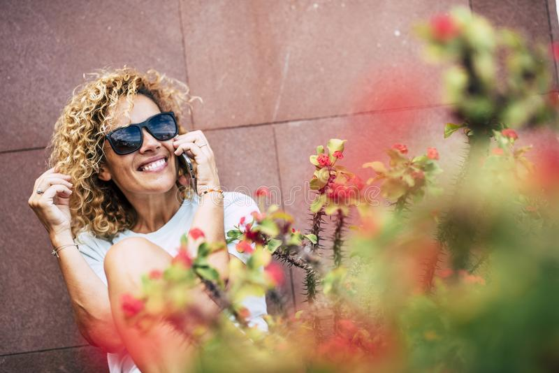 Cheerful adult young people woman talk at the phone sitting outdoor with flowers and red wall in background -female. and. Technology in leisure activity royalty free stock images