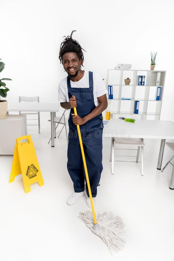 cheerful african american cleaner holding mop and smiling stock image