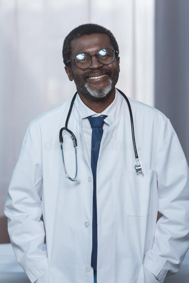 Cheerful african american doctor in white coat with stethoscope looking. At camera stock photography