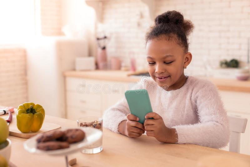 Cheerful African-American girl watching cartoon on the smartphone stock photography
