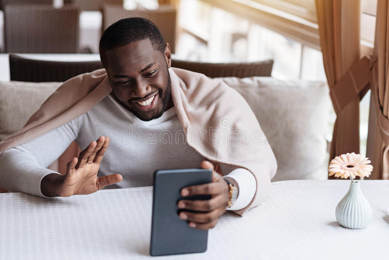 Cheerful African American man having the conversation via the Internet royalty free stock image