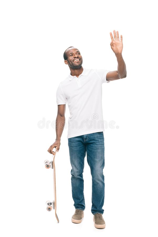 cheerful african american man holding skateboard and waving hand stock photography