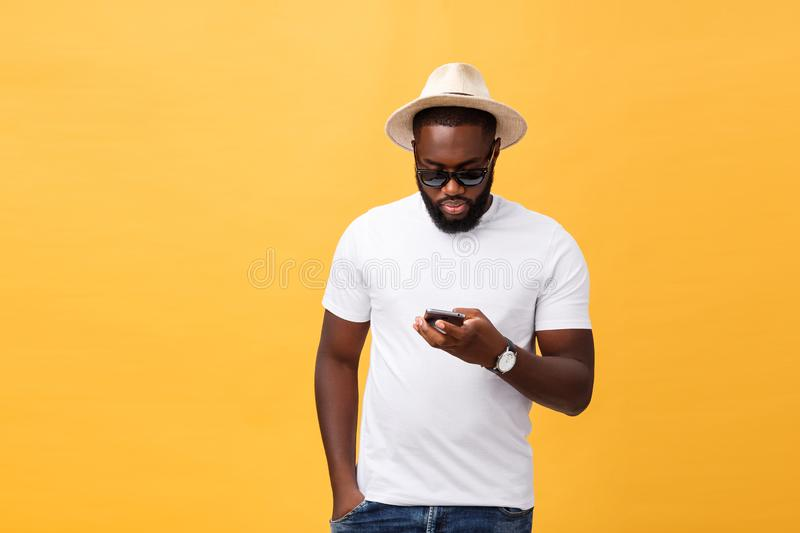 Cheerful African American man in white shirt using mobile phone application. happy dark skinned hipster guy read news. From social network in mobile phone stock images