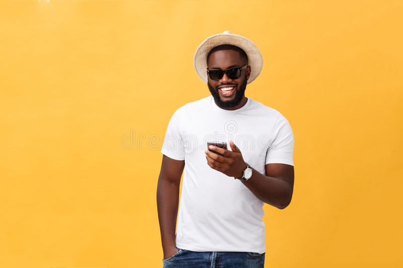 Cheerful African American man in white shirt using mobile phone application. happy dark skinned hipster guy read news. From social network in mobile phone royalty free stock image