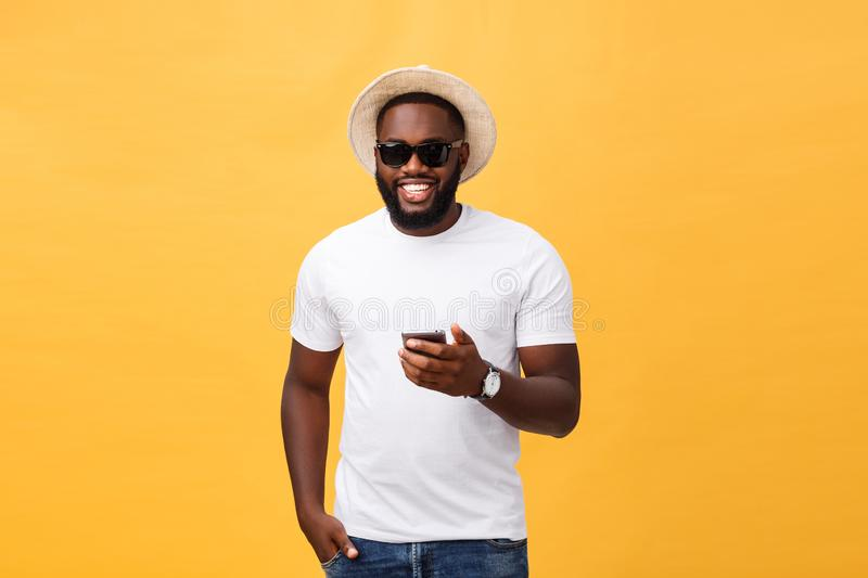 Cheerful African American man in white shirt using mobile phone application. happy dark skinned hipster guy read news. From social network in mobile phone royalty free stock images