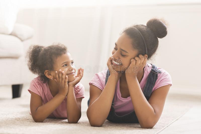 Cheerful african american sisters lying on floor and smiling to each other royalty free stock images