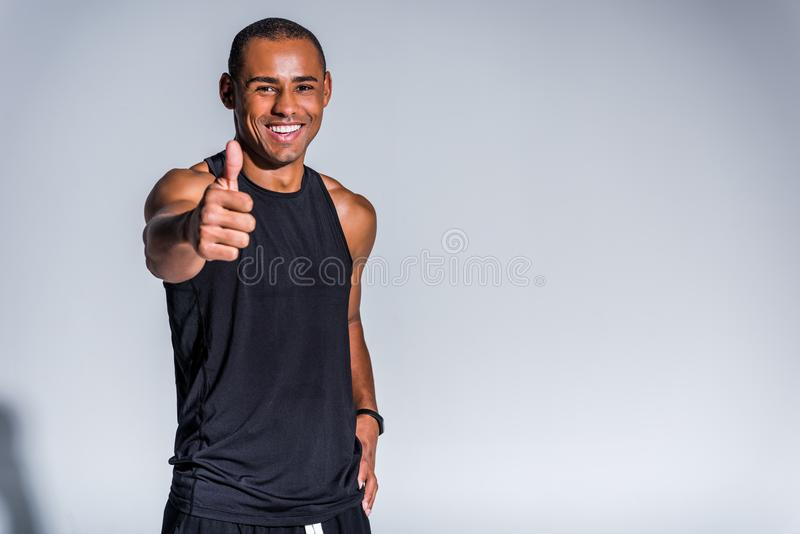 cheerful african american sportsman showing thumb up and smiling at camera stock photography