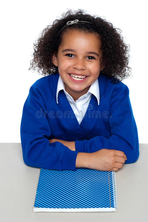 Cheerful African American student. Cheerful African American relaxed student facing camera and smiling. Notebook beneath her crossed arms royalty free stock photos