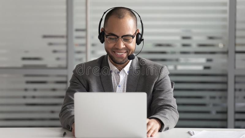 Cheerful african american support service male worker consulting corporate customer. Cheerful african american support service male worker in eyeglasses wearing stock images