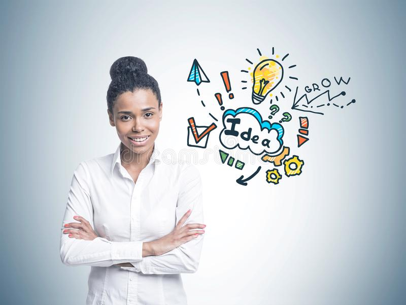 Cheerful African American woman, business idea. Smiling confident young African American woman wearing a white shirt and black pants standing with crossed arms royalty free stock photo