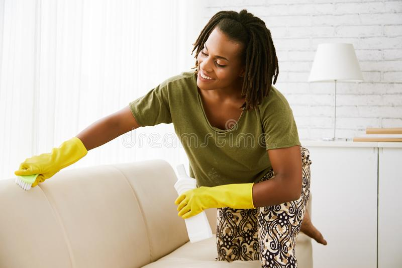 Housewife cleaning sofa stock photography