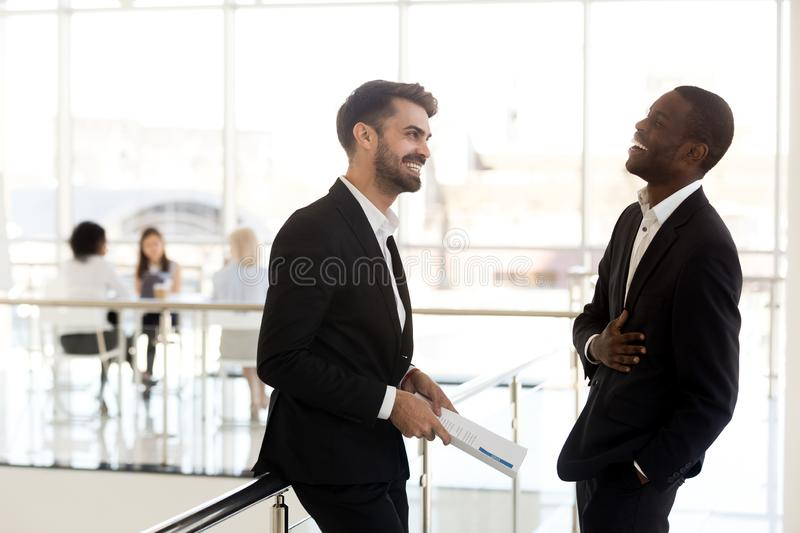 Cheerful african businessman laughing at funny joke of caucasian royalty free stock photos