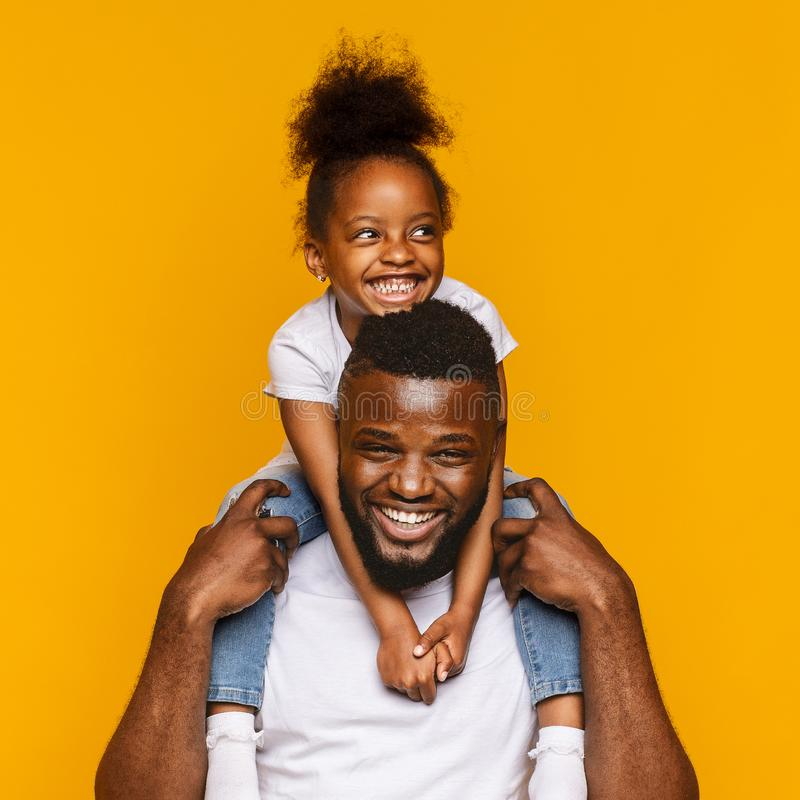 Cheerful african dad riding his cute little daughter on shoulders stock images