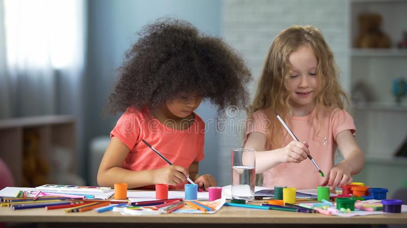 Cheerful African and European girls sitting at the table and painting, hobby royalty free stock photography