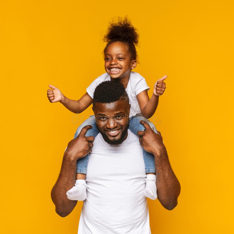 Cheerful african girl gesturing thumbs up, sitting on daddy`s shoulders stock photos