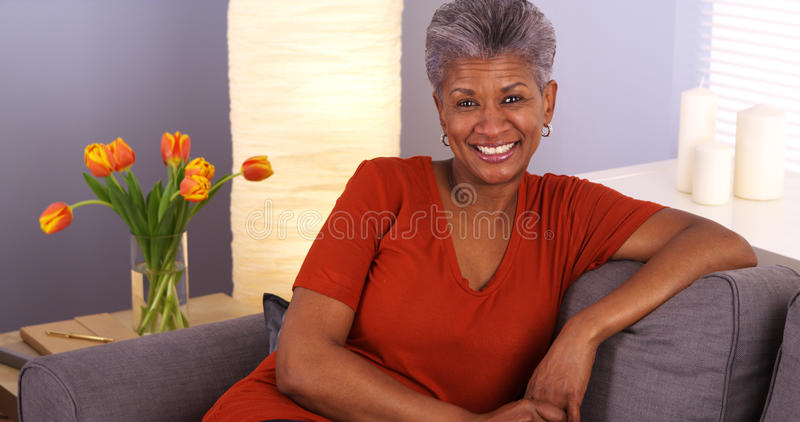 Cheerful African grandmother sitting on couch royalty free stock photo