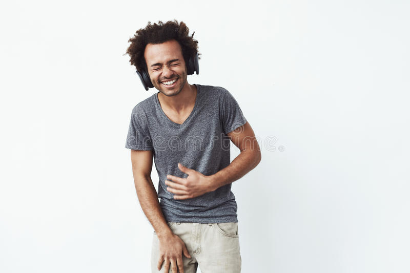 Cheerful african man in headphones laughing over white background. Closed eyes. Cheerful african man in headphones laughing over white background. Copy space royalty free stock photo
