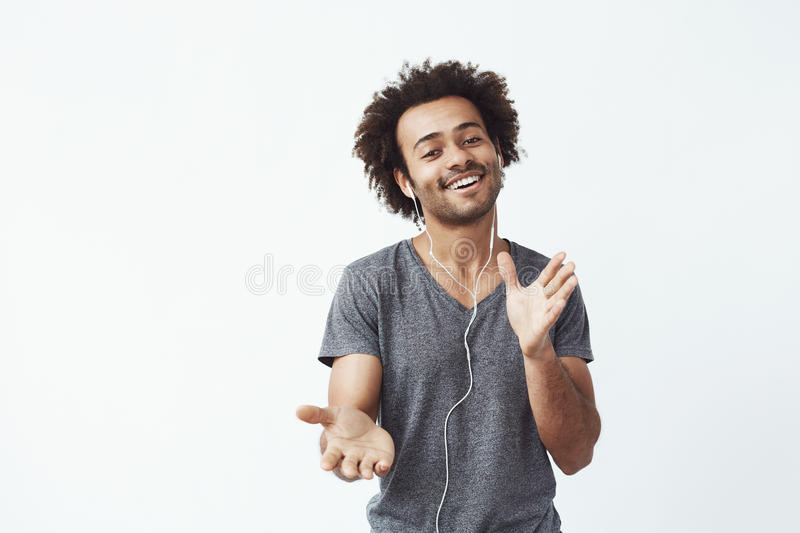 Cheerful african man listening to music in headphones dancing singing. White background royalty free stock photos