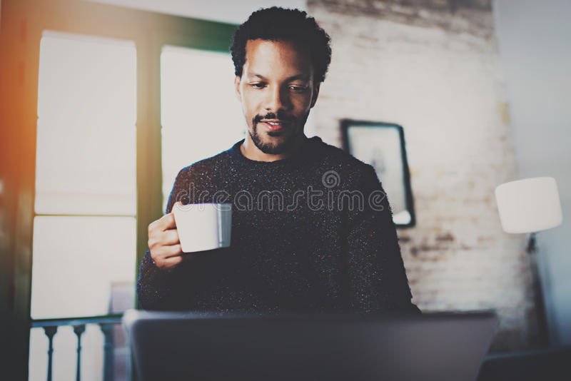 Cheerful African man using computer and smiling at the living room.Black guy holding ceramic cup in hand.Concept of stock photos