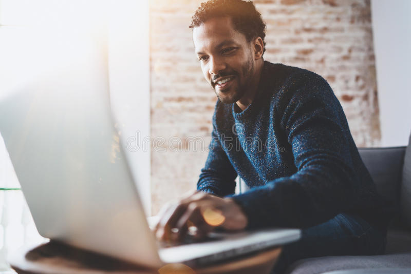 Cheerful African man using computer and smiling while sitting on the sofa.Concept of young business people working at stock image