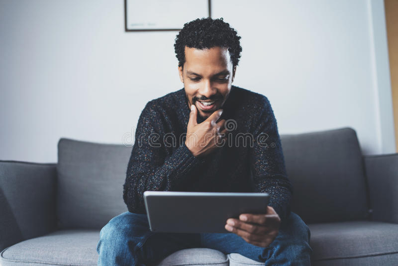 Cheerful African man using pc tablet and smiling while sitting on the sofa in his modern room.Concept of young business stock photography