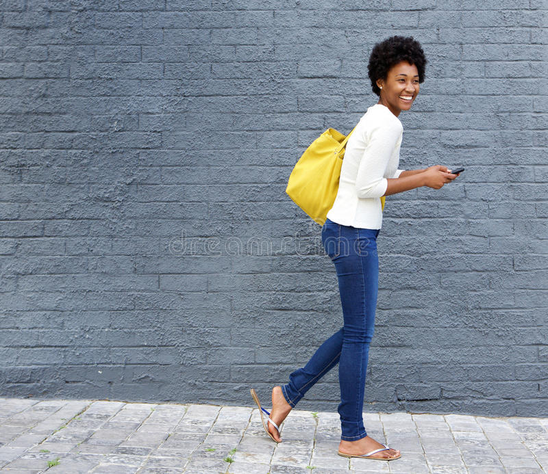Cheerful african woman walking on street with mobile phone. Full length portrait of a cheerful young african woman walking on street with a mobile phone stock images