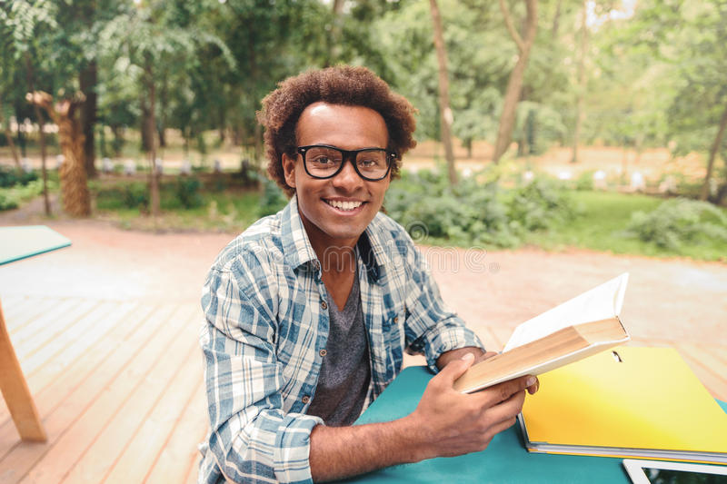 Cheerful african young man reading book outdoors royalty free stock photos