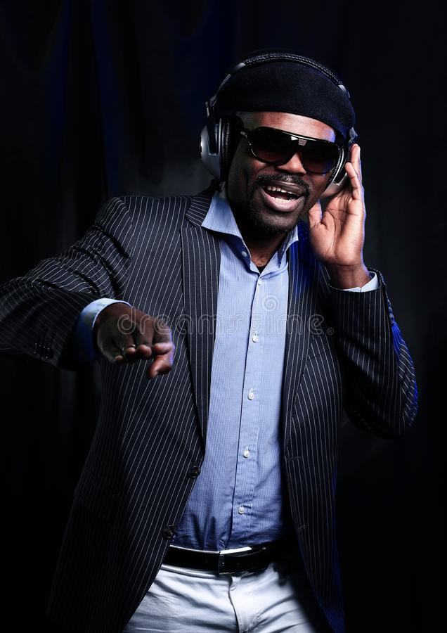African American male DJ playing music at a party. Cheerful afro american man in stylish cloth and glasses posing over black background royalty free stock image