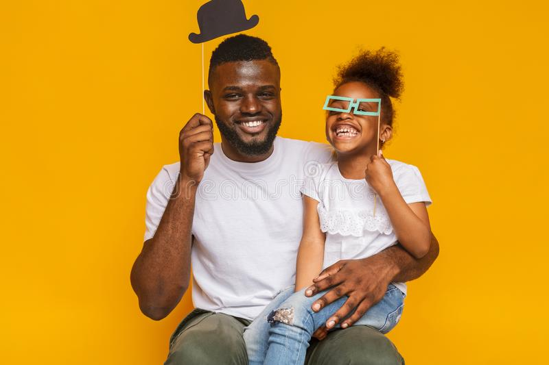Cheerful afro father and daughter posing with photo props. Family fun. Cheerful afro father and daughter posing with photo props, orange studio background royalty free stock photography