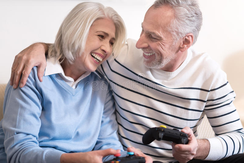 Cheerful aged couple relaxing at home royalty free stock photography