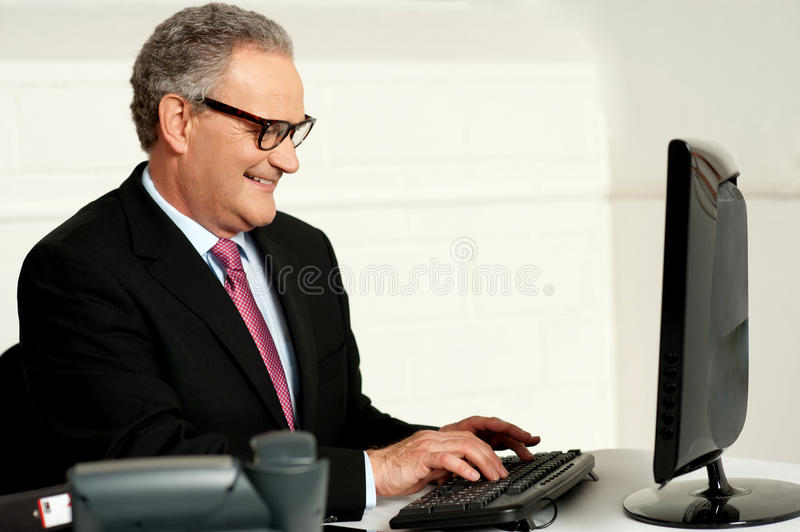 Cheerful aged man working on computer royalty free stock photography