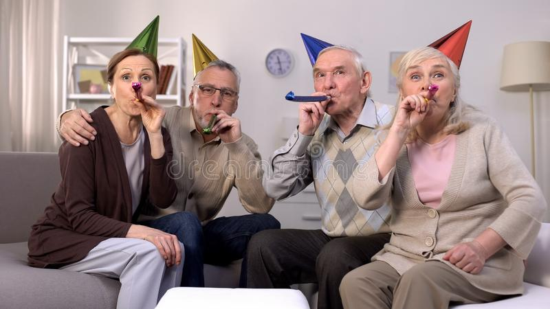 Cheerful aged people birthday hats blowing party horns, holiday celebration, fun stock photo