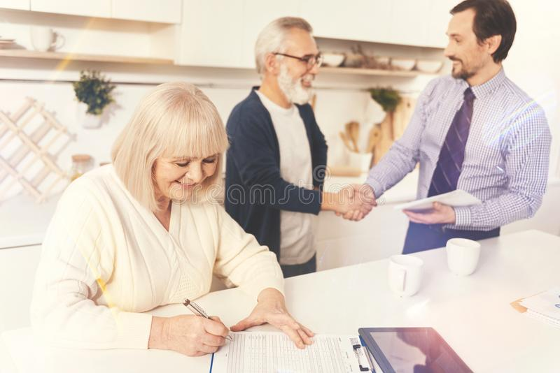 Cheerful aged woman signing papers. Come to agreement. Cheerful aged women signing papers while her husband and real estate agent shaking hands while standing in royalty free stock photo
