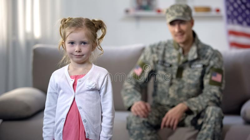 Cheerful american soldier dad admiring cute daughter looking at camera, pride. Stock photo stock photography