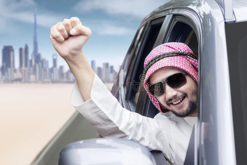 Cheerful Arabic person driving a car. Image of successful Arabic person driving a car while raising his hand and wearing sunglasses stock photo