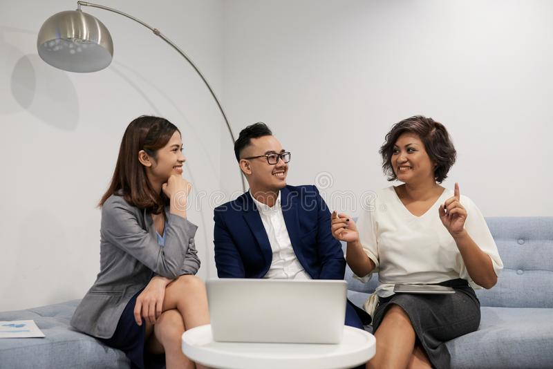 Business woman telling idea. Cheerful Asian business lady telling her idea to coworkers at meeting royalty free stock photo