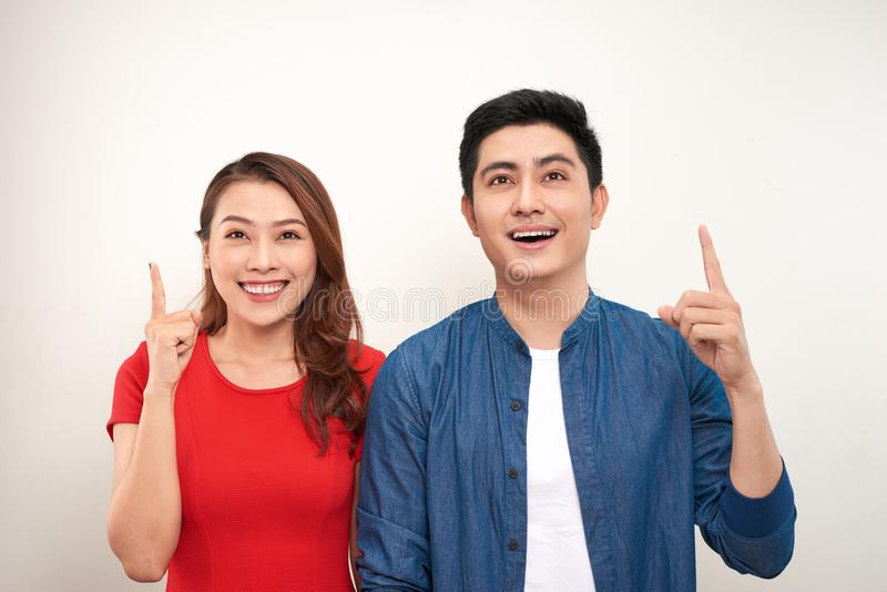 Cheerful asian couple standing isolated over white background, pointing fingers stock photography