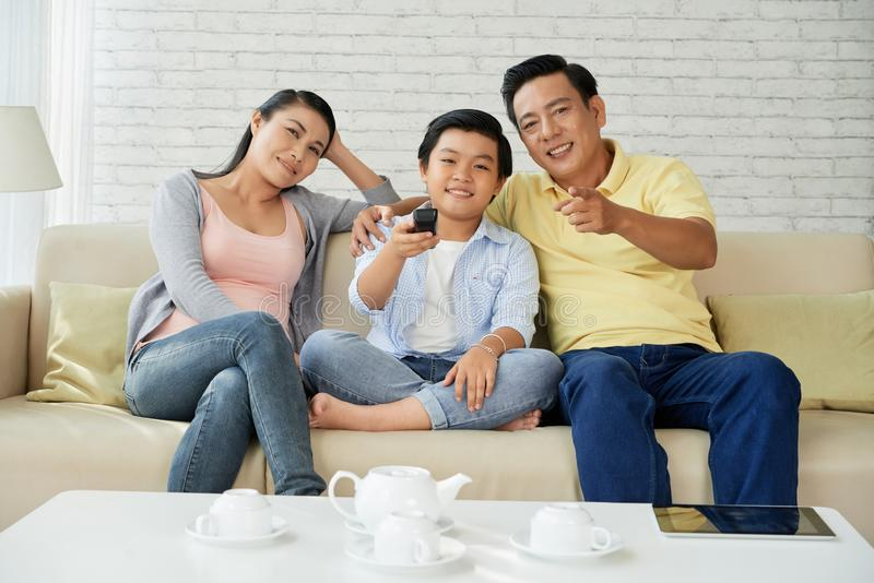 Family watching tv. Cheerful Asian family sitting on comfy sofa at home and watching television royalty free stock image