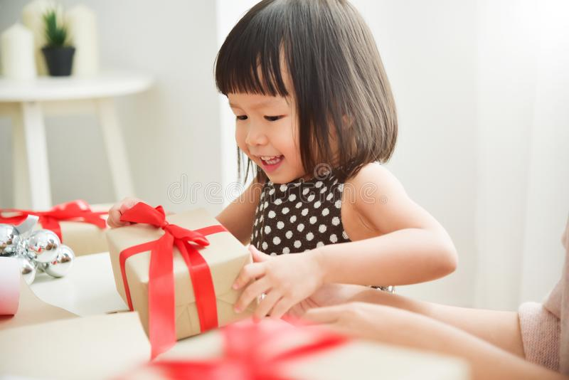 Cheerful Asian little kid celebrating with a gift box. Cheerful Asian little kid celebrating with a brown gift box for Birthday, Christmas and New year in a royalty free stock photography