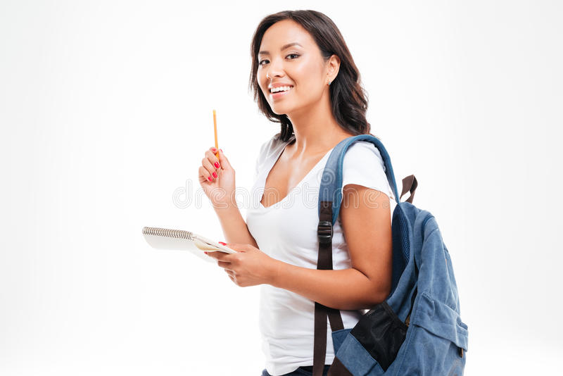 Cheerful asian teen girl have an idea and holding notebook royalty free stock photography