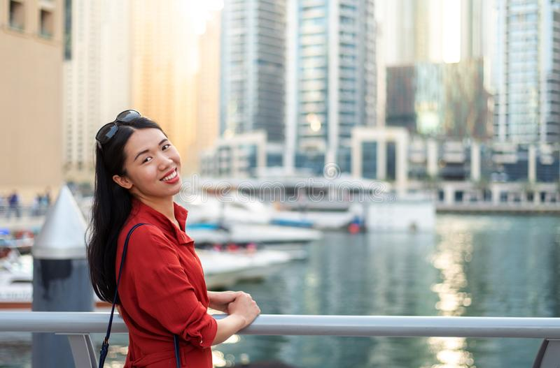 Cheerful Asian tourist in Dubai marina. Cheerful female Asian tourist in Dubai marina woman travel chinese girl uae red luxury day portrait cityscape business stock image