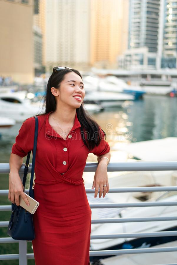 Cheerful Asian tourist in Dubai marina. Cheerful female Asian tourist in Dubai marina woman travel chinese girl uae red luxury day portrait cityscape business stock photos