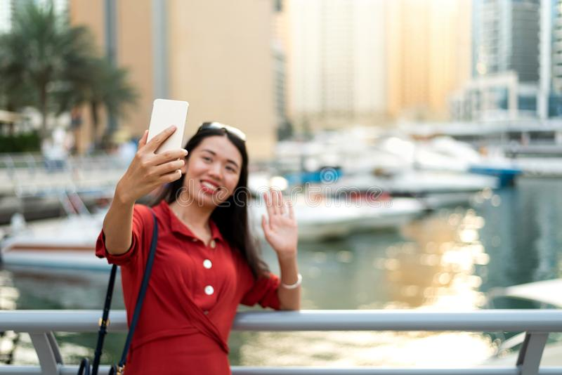 Asian tourist taking selfie in Dubai marina. Cheerful Asian tourist taking selfie in Dubai marina woman take phone smart alone mobile online device portable stock photography