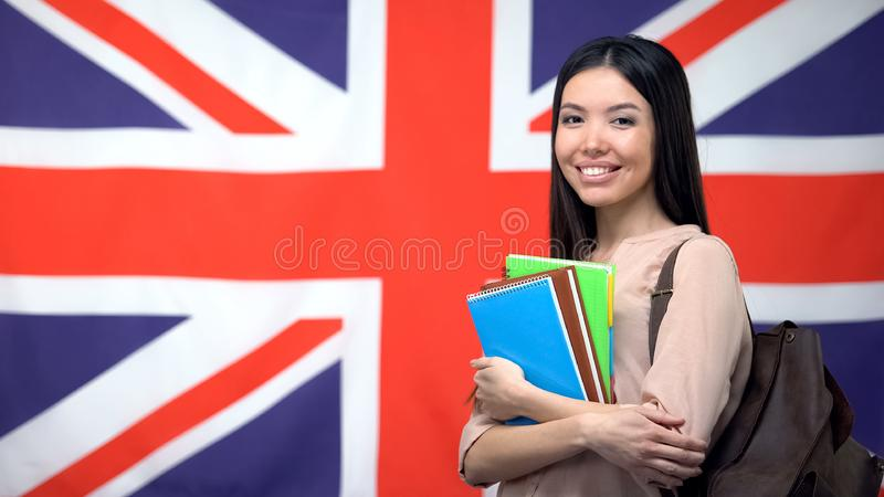 Cheerful Asian woman standing against British flag background, study abroad royalty free stock images