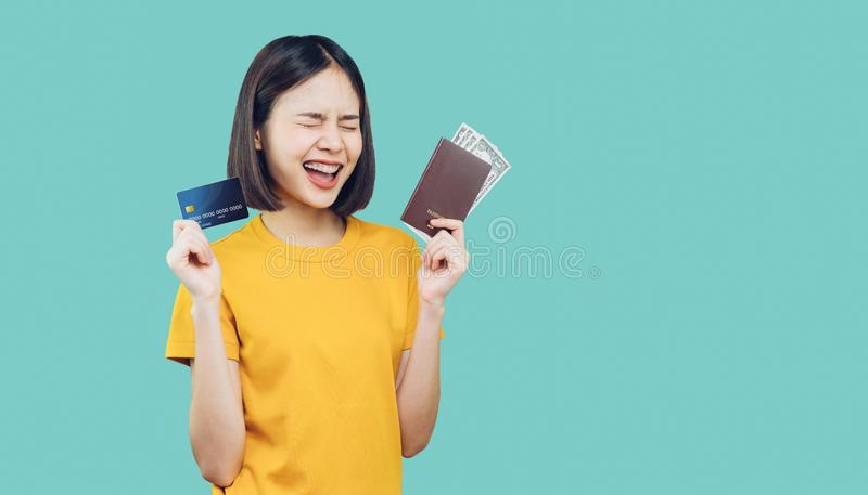 Cheerful Asian woman in yellow t-shirt holding credit card and passport with dollar money to travel on weekends getaway. Cheerful Asian woman in yellow t-shirt stock photography