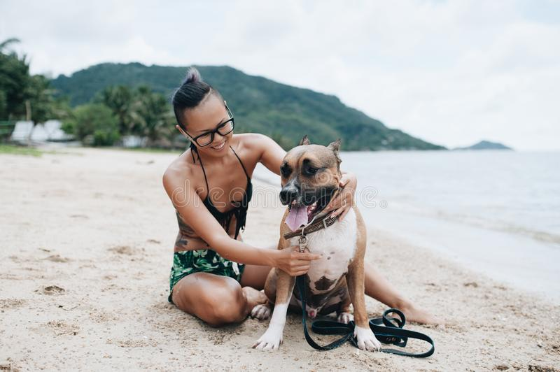 Cheerful asian young woman in eyeglases sitting and hugging her dog on the beach royalty free stock images