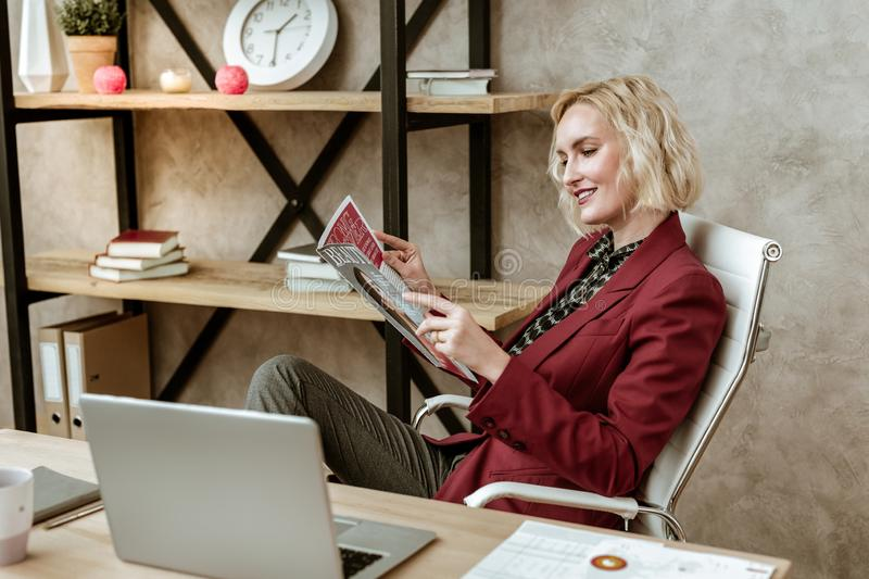 Cheerful attentive woman resting on white office armchair. Appealing fit woman. Cheerful attentive woman resting on white office armchair and flipping through royalty free stock photography