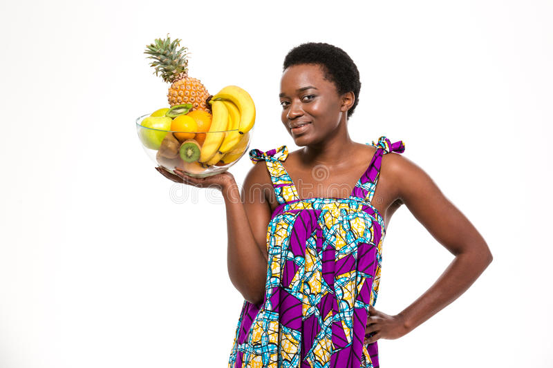 Cheerful attractive african american woman holding glass bowl with fruits royalty free stock photo