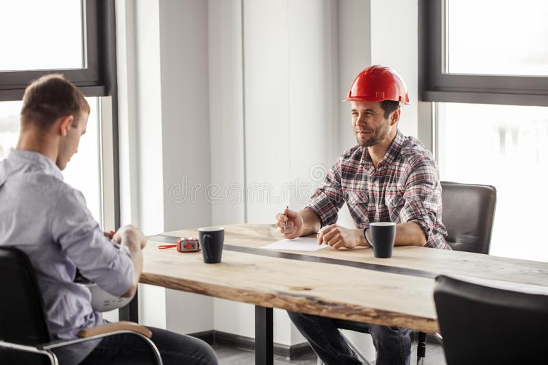 Cheerful attractive man is sitting with a pen and paper royalty free stock photo